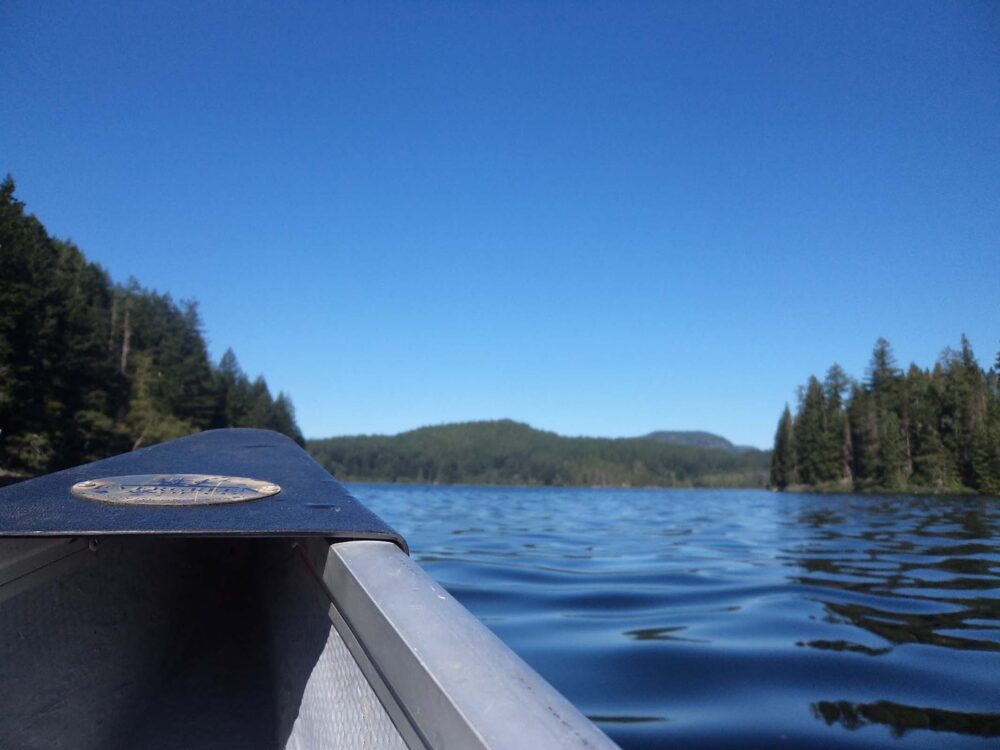 Close up view of canoe bow with calm lake water and forest behind on Main Lake, one of the best BC canoe trips