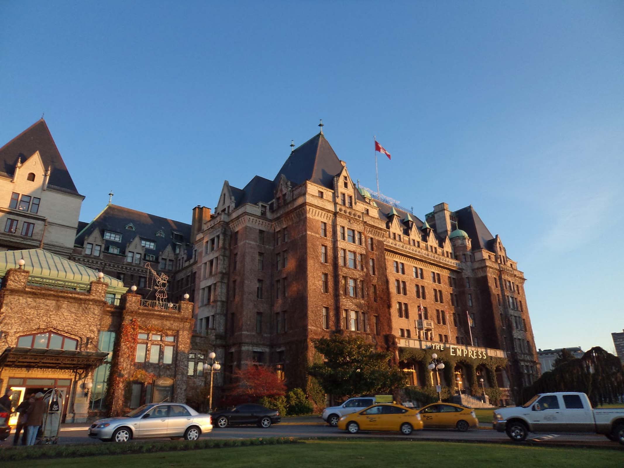 A regal looking hotel with Canadian flag and many taxis outside