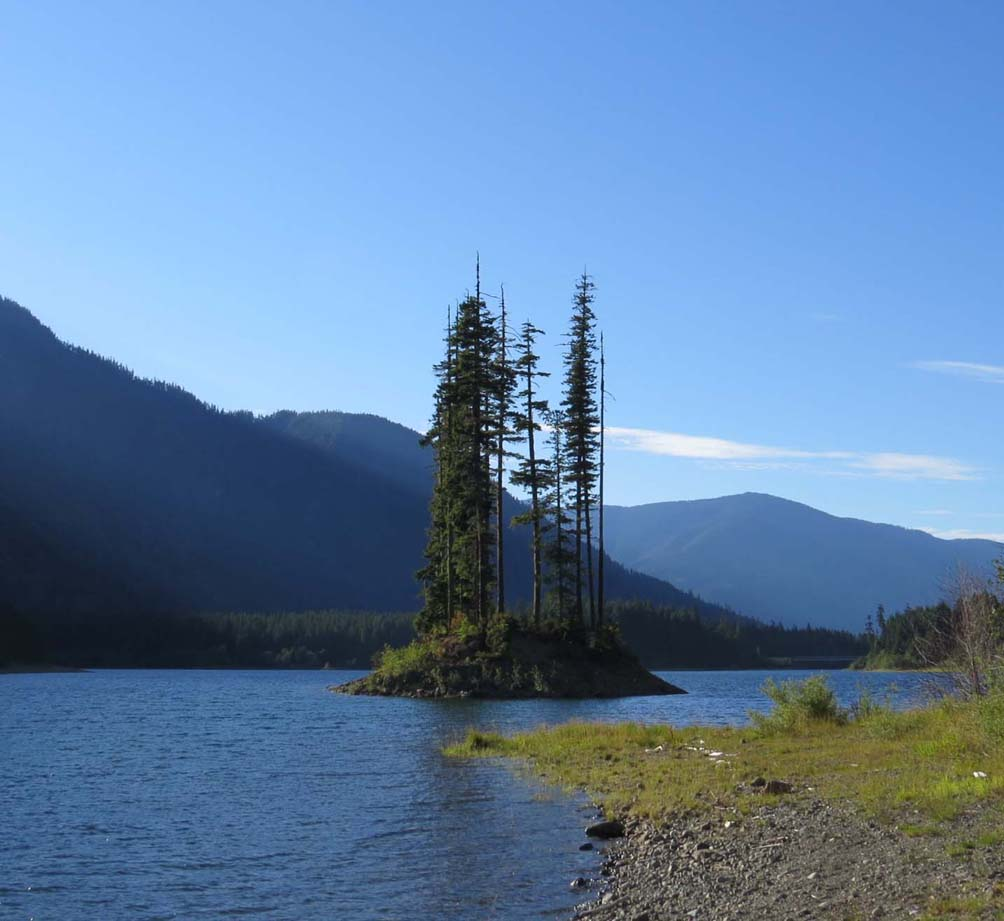 Calm Buttle lake surrounded by steep mountains, with tree covered island
