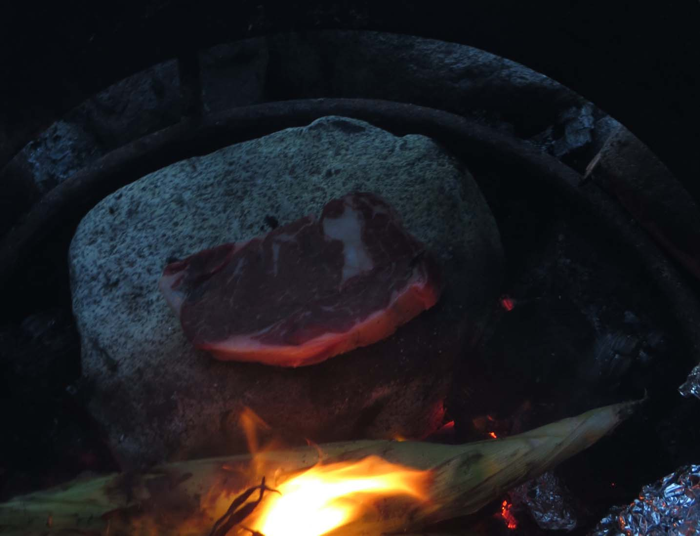 Steak cooking on stone in campfire