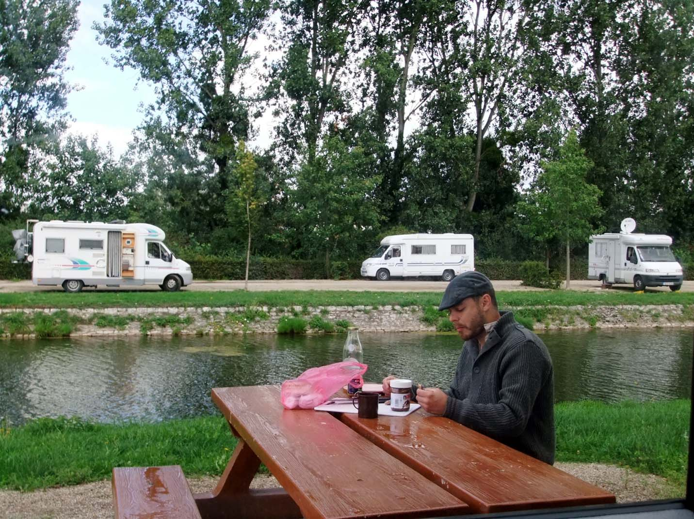JR eating lunch with campervans behind at the aire de service, France