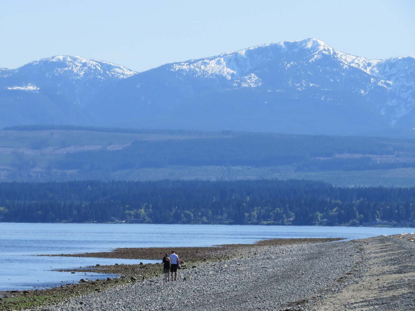 Couple walking on beach with mountains behind - Goose Spit is one of the best beaches in British Columbia