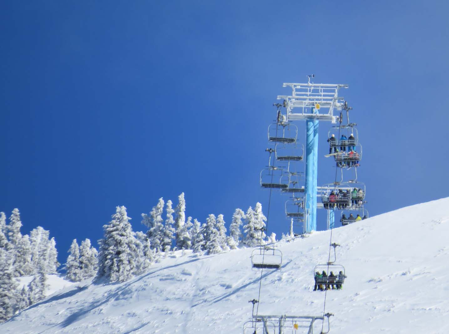Close up of skiers and snowboards riding a chairlift at Mount Washington Ski Resort on Vancouver Island