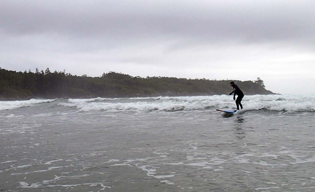 Catching the waves while surfing in Tofino, Canada