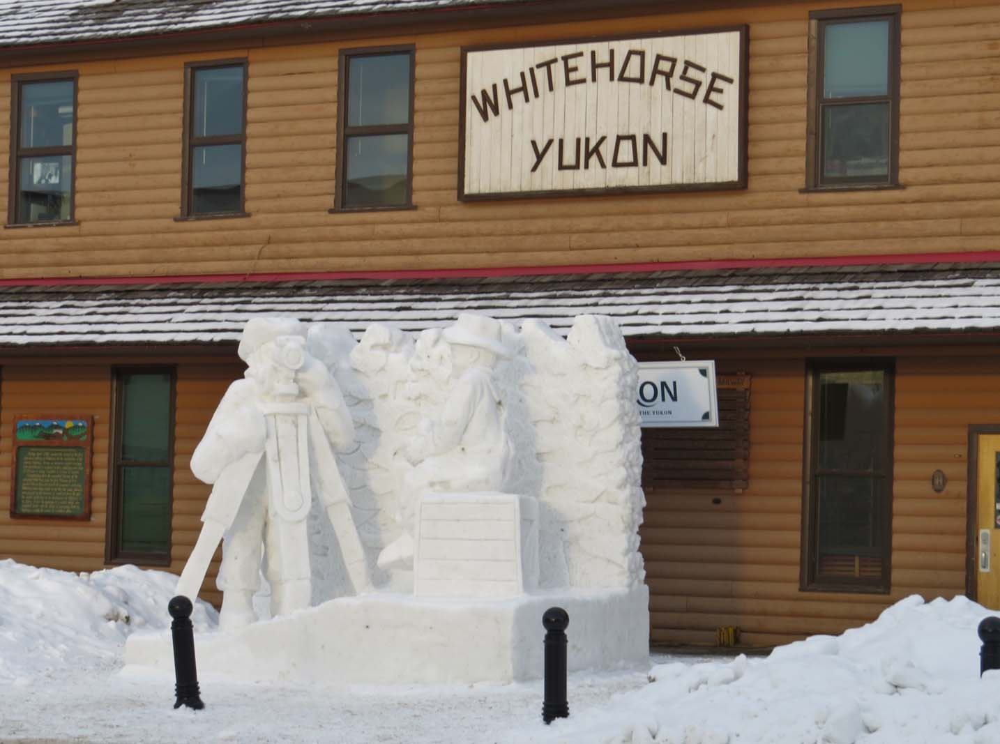 Carved ice sculpture in front of wooden building
