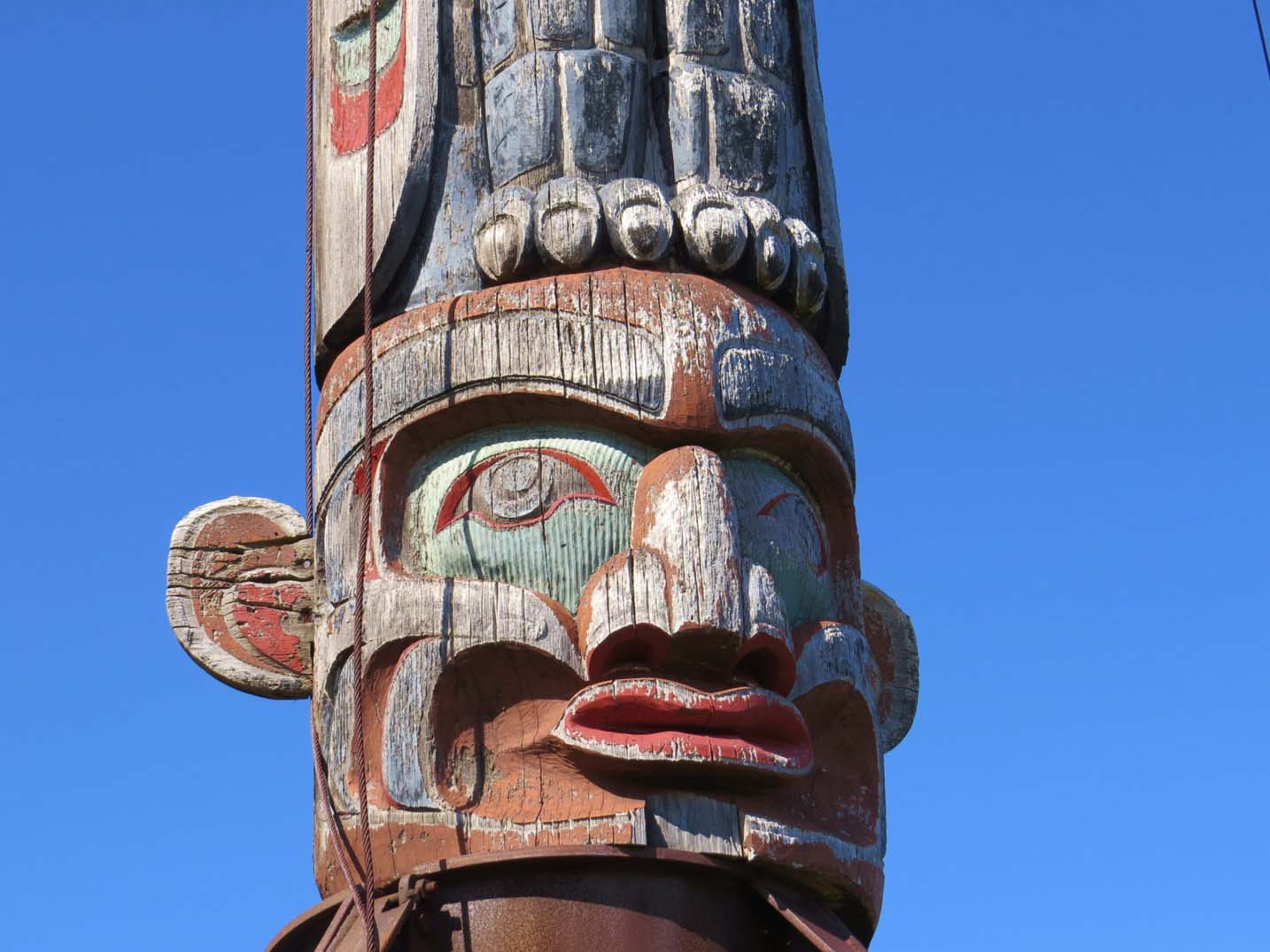 Carved wooden totem pole with face and eagle claws