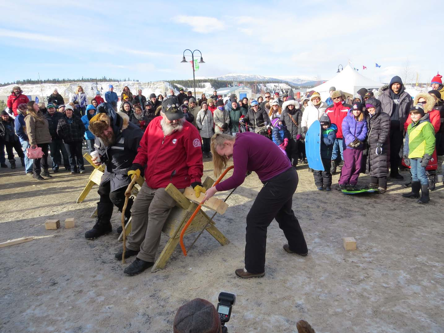 Woman sawing a log in front of a crowd