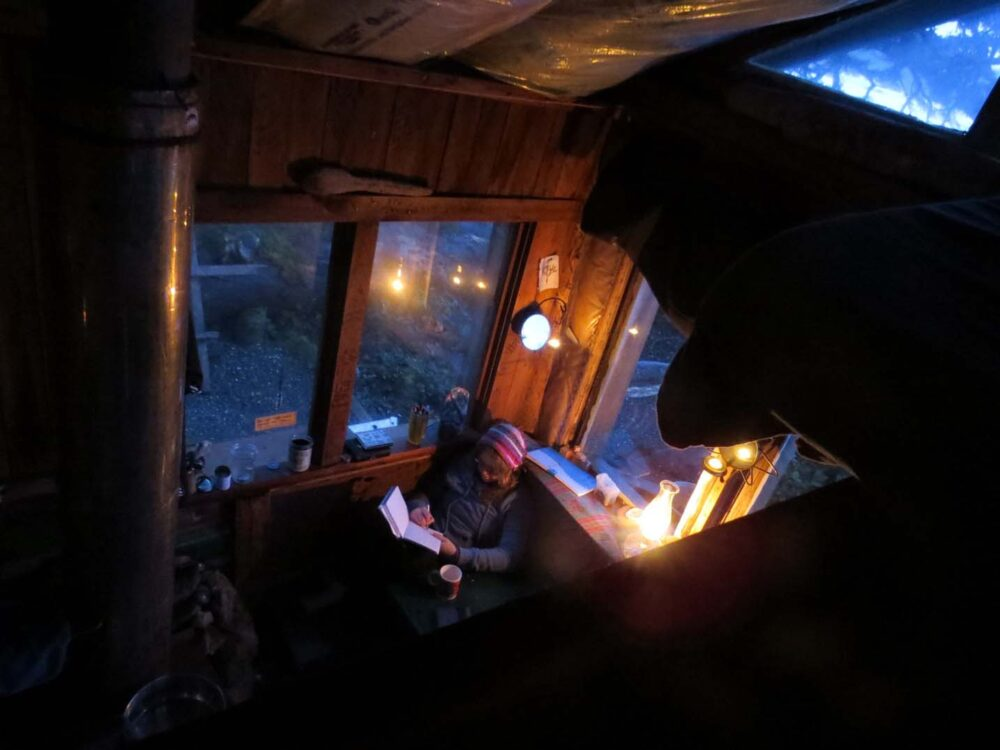 Gemma reading by wood stove in cabin