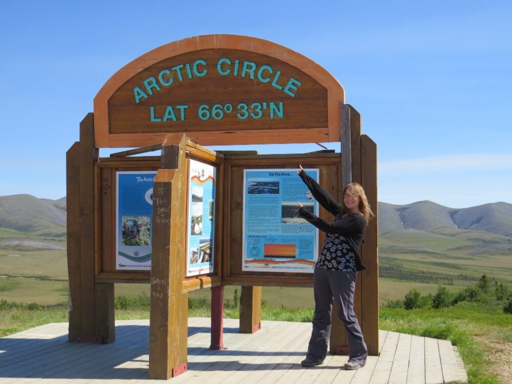 Gemma pointing to a wooden Arctic Circle sign