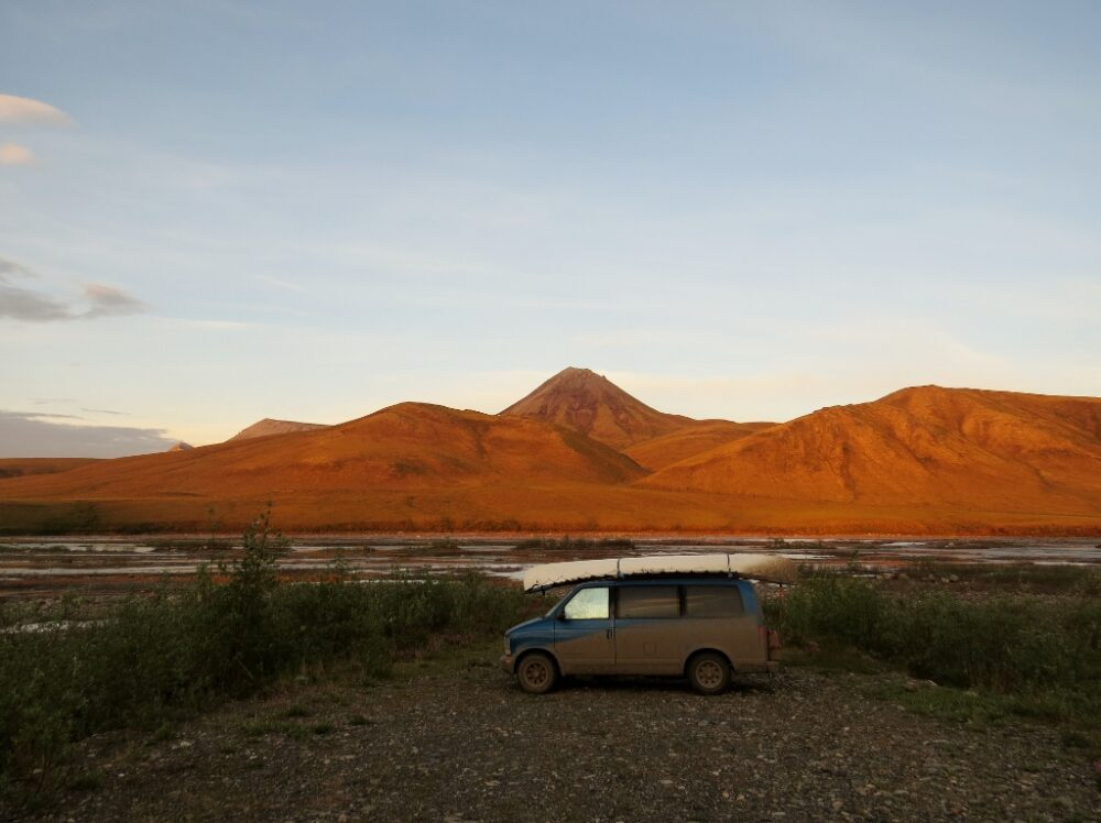 Dirty van with mountains in background, lit up red by sunset