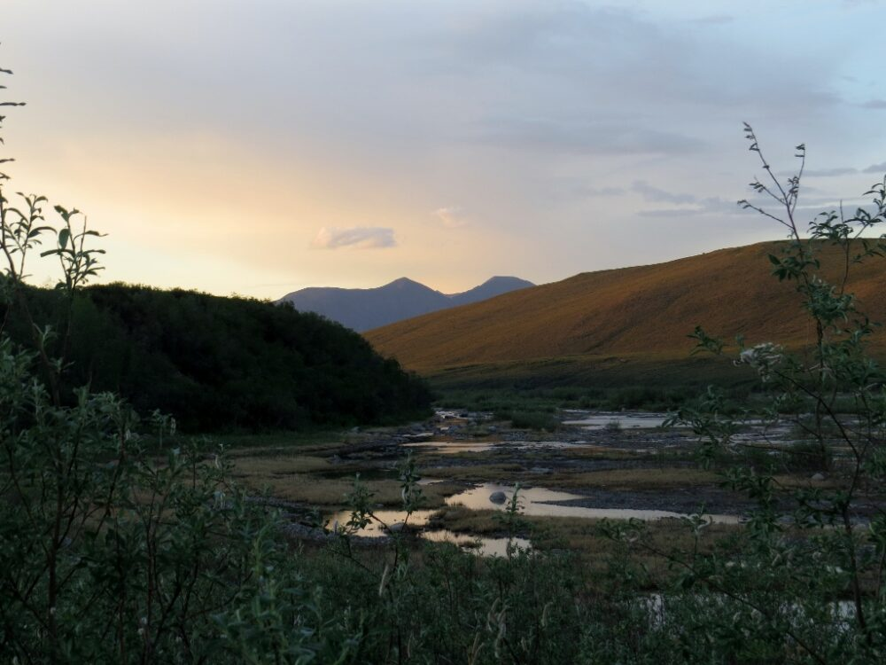 Riverbed with sunset and mountains behind