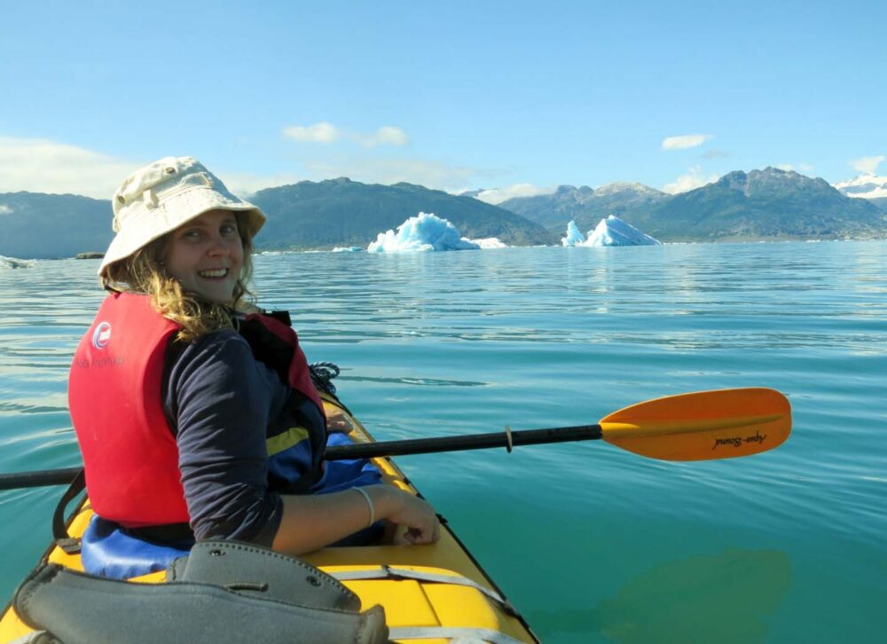 Gemma kayak paddling in Prince William Sound, Alaska with icebergs in background