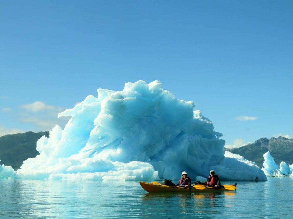 Gemma in yellow kayak in front of large iceberg