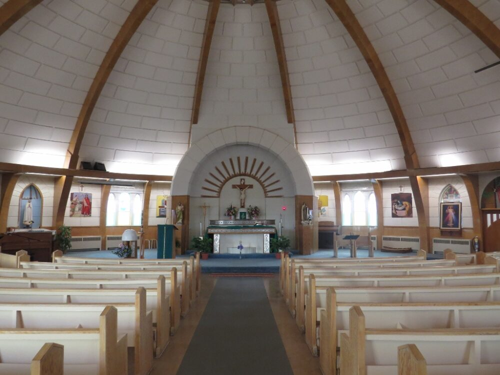 Curved white blocks with white seating and a simple altar in the igloo church