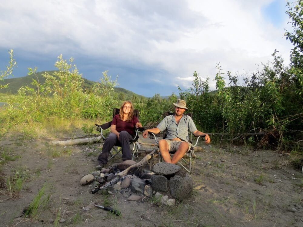 JR and Gemma sat behind a campfire