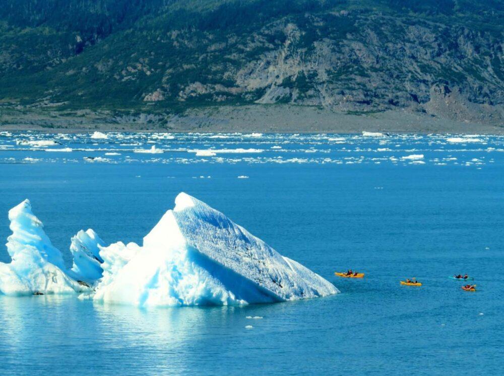 Kayaking in Alaska, kayakers approaching iceberg