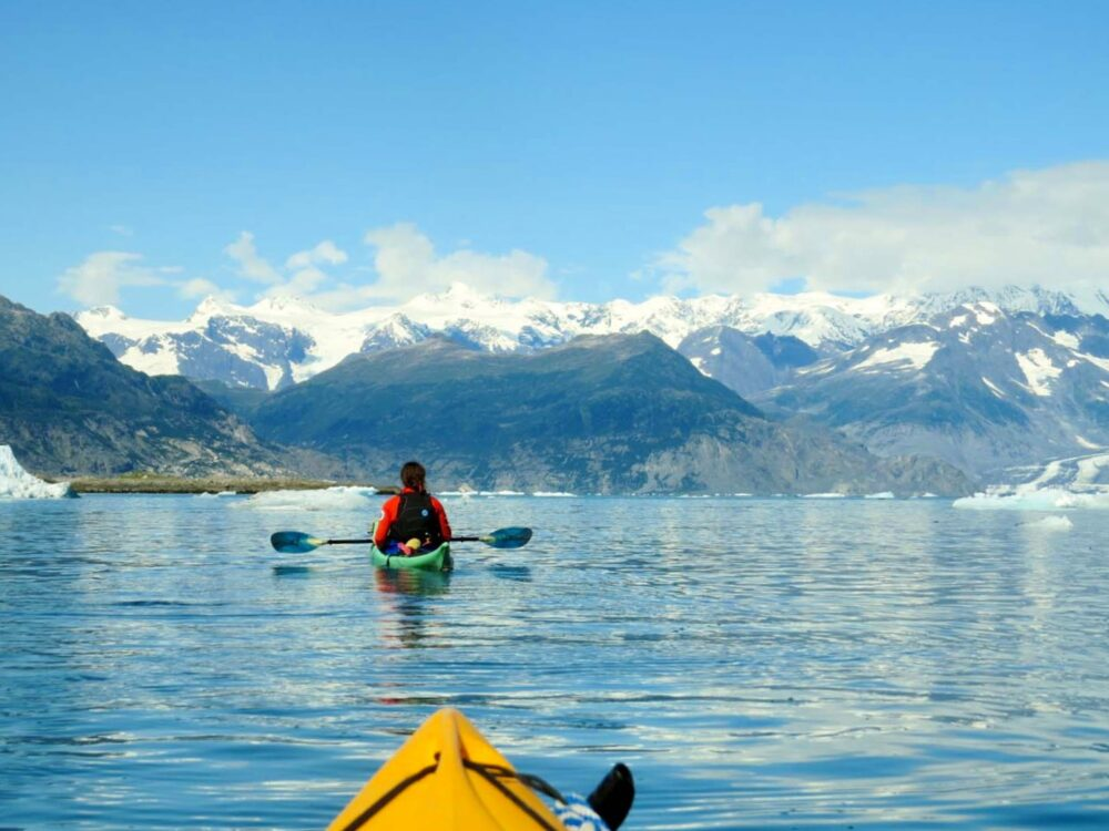 Kayaking in Alaska with icebergs following tour guide