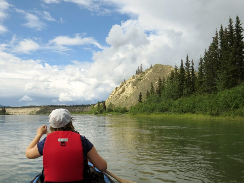 Back view of Gemma paddling a canoe on wide river