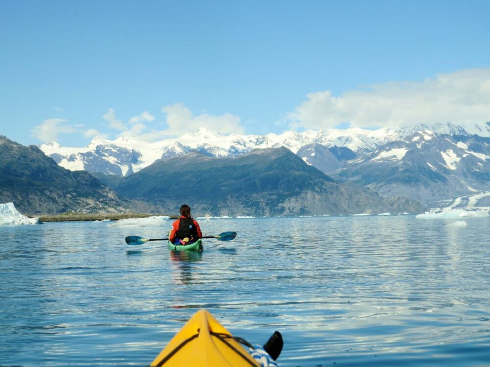 Mountain range and icebergs, approached by kayak