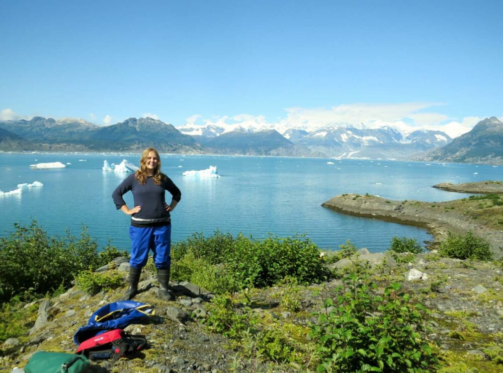 Gemma standing in front of mountain view wearing kayaking gear