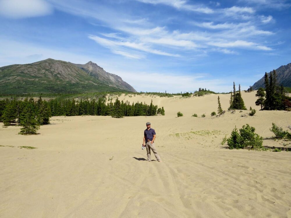JR stands in the middle of a sandy desert, with high hills behind - the Carcross Desert, another must see on a Yukon road trip