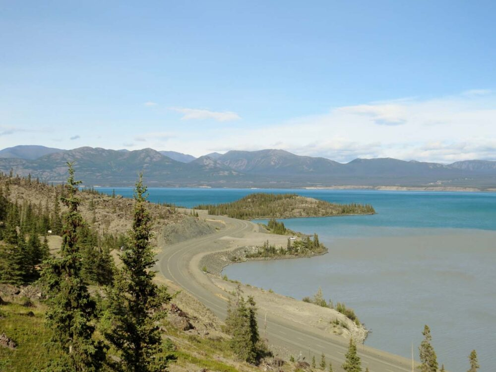 The Alaska Highway winds around the shores of brightly coloured Kluane Lake