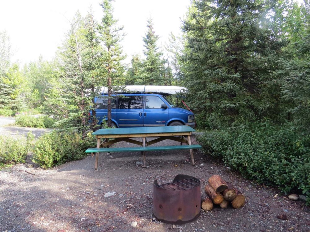 Firepit, wood and picnic table with blue van in background at Million Dollar Falls campground in Yukon