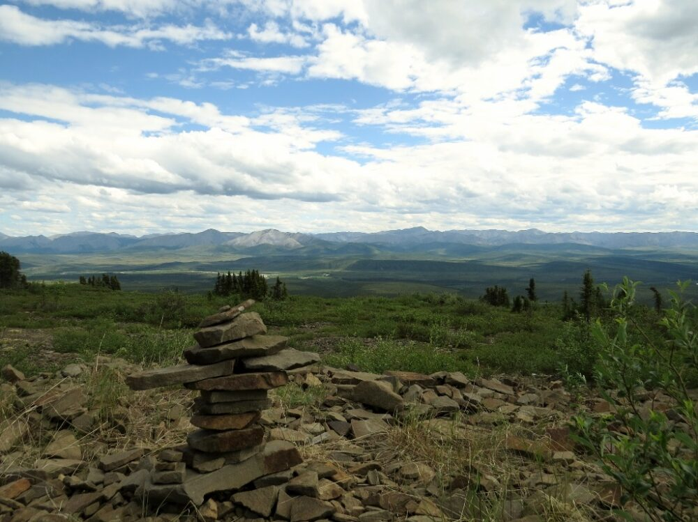 Stack of rocks (inukshuk) looks out onto the green landscape on the Dempster Highway - one of the best road trips in the Yukon