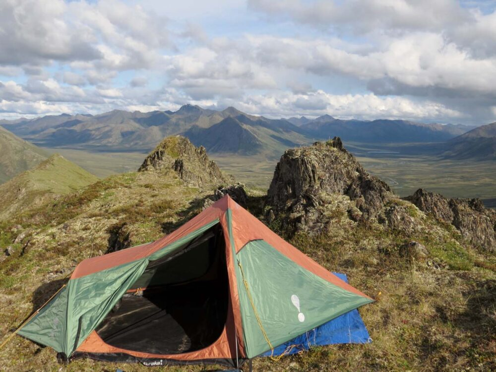 Green and orange tent pitched at top of mountain with peaks beyond