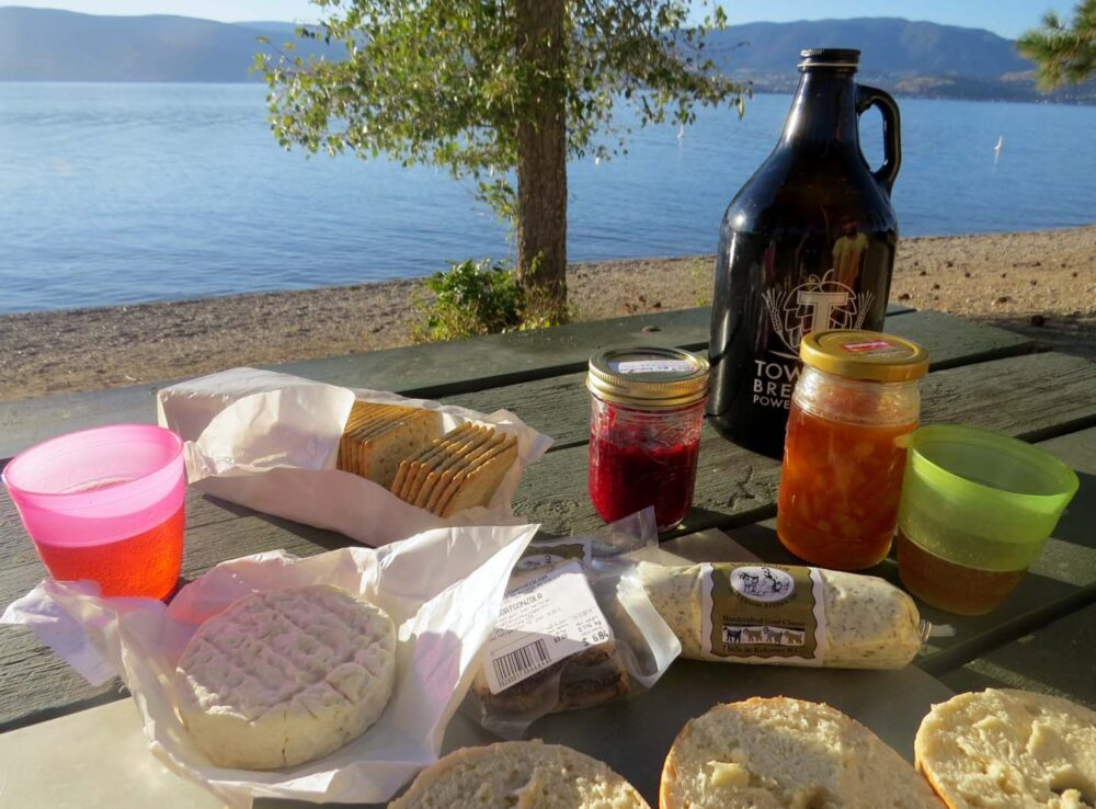 Cheese, crackers, bread and beer on a picnic table by the beach
