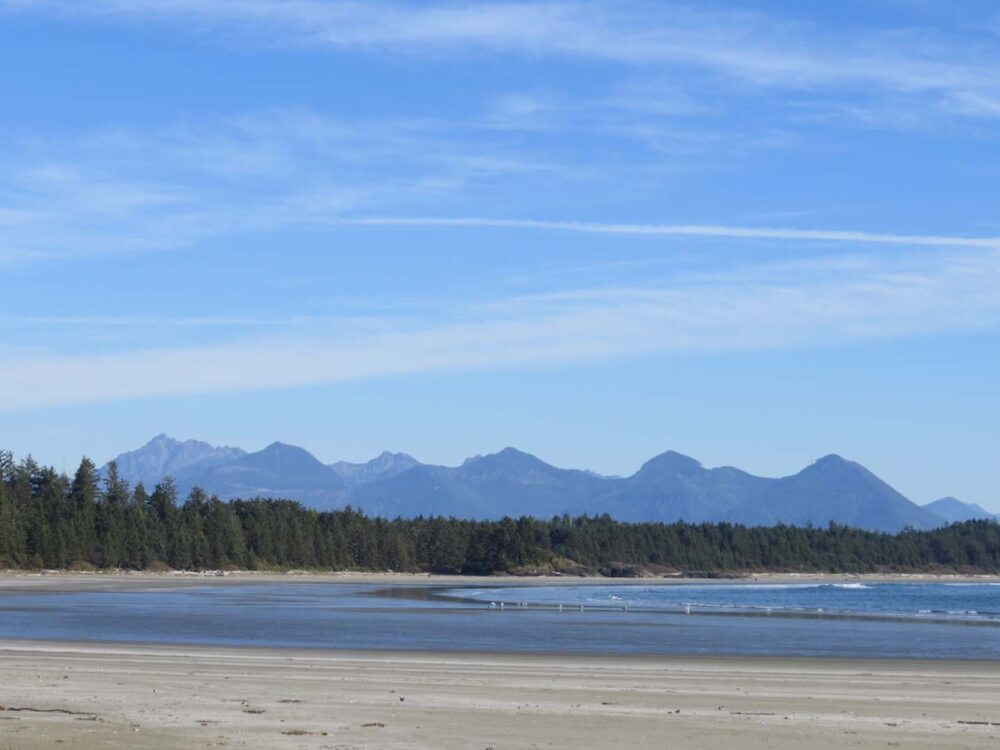 Flat sandy beach with low tide ocean and mountains behind