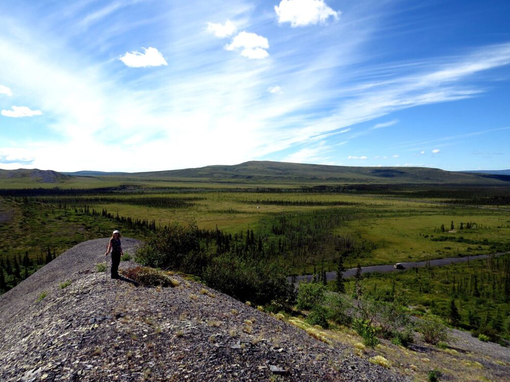 A hiker stands ontop a hill looking out to sweeping views of tundra