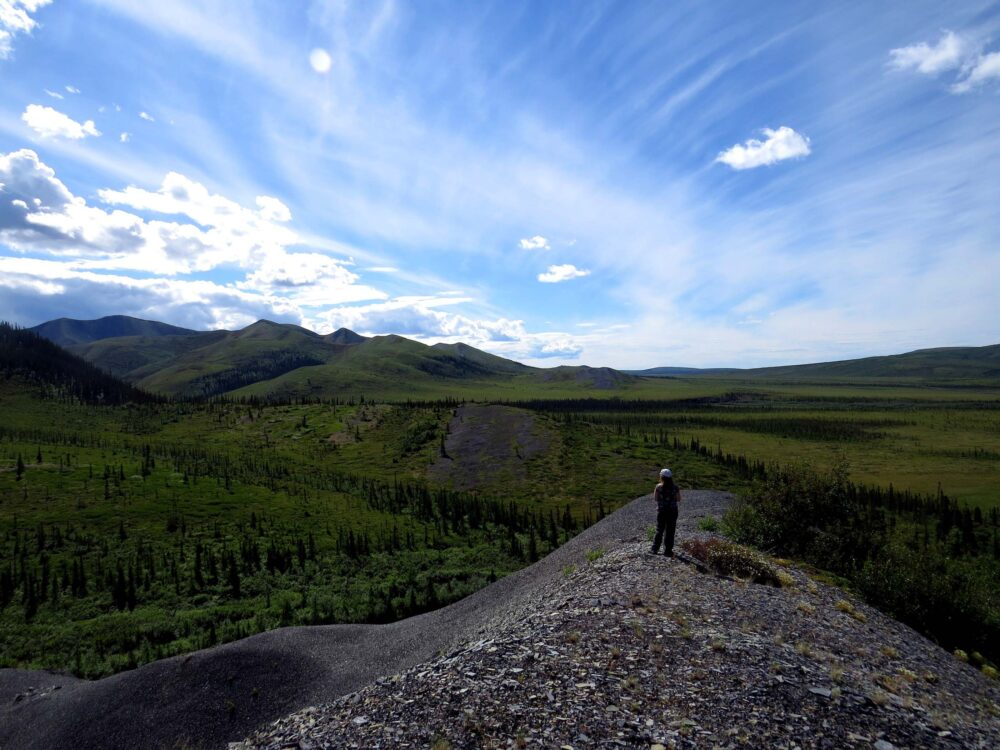 Gemma hiking near the Dempster Highway with far reaching views of tundra