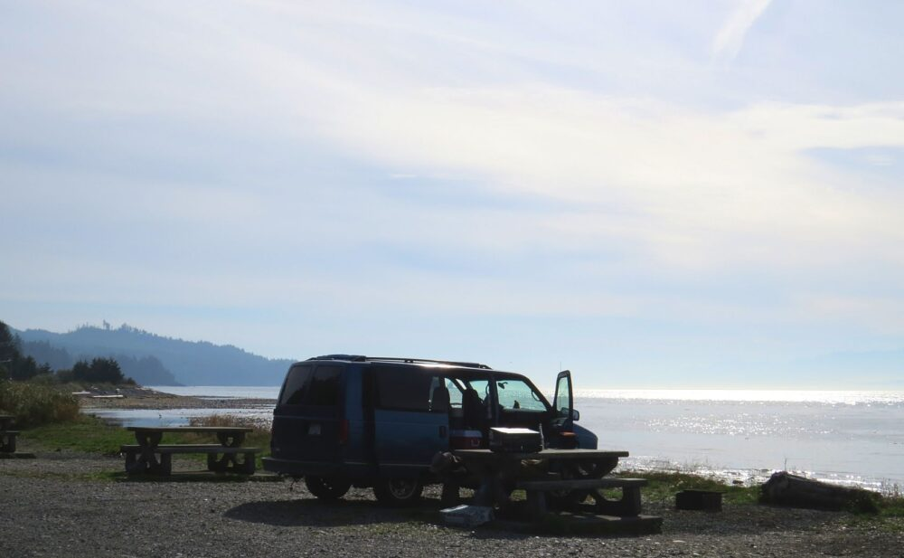 A van is parked next to a picnic table at Jordan River campground, with the doors open