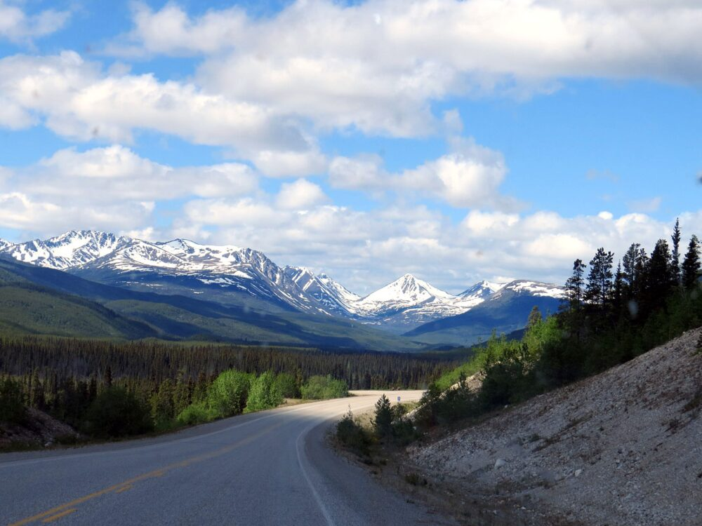 Driving a road in Yukon, with mountains in the background and trees in the foreground