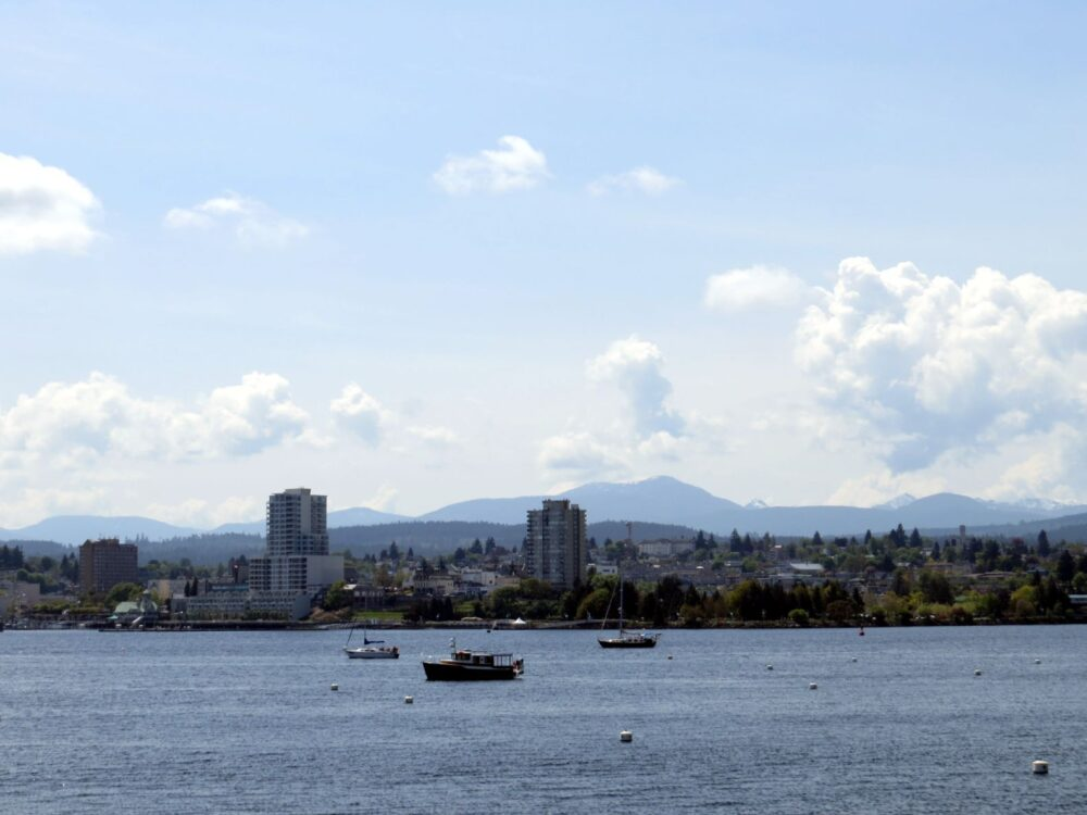 Highrise buildings and apartment blocks of Nanaimo as seen from Newcastle Island, with boats and ocean in foreground
