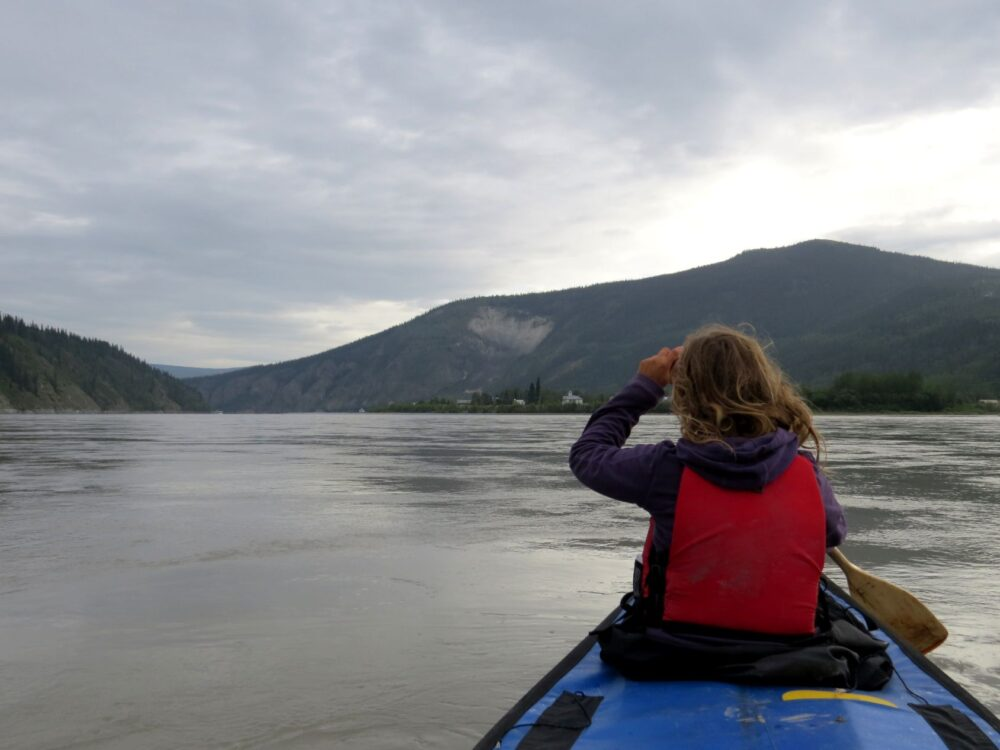 Gemma paddling at the front of the canoe, looking out to Dawson City, Yukon, in the distance