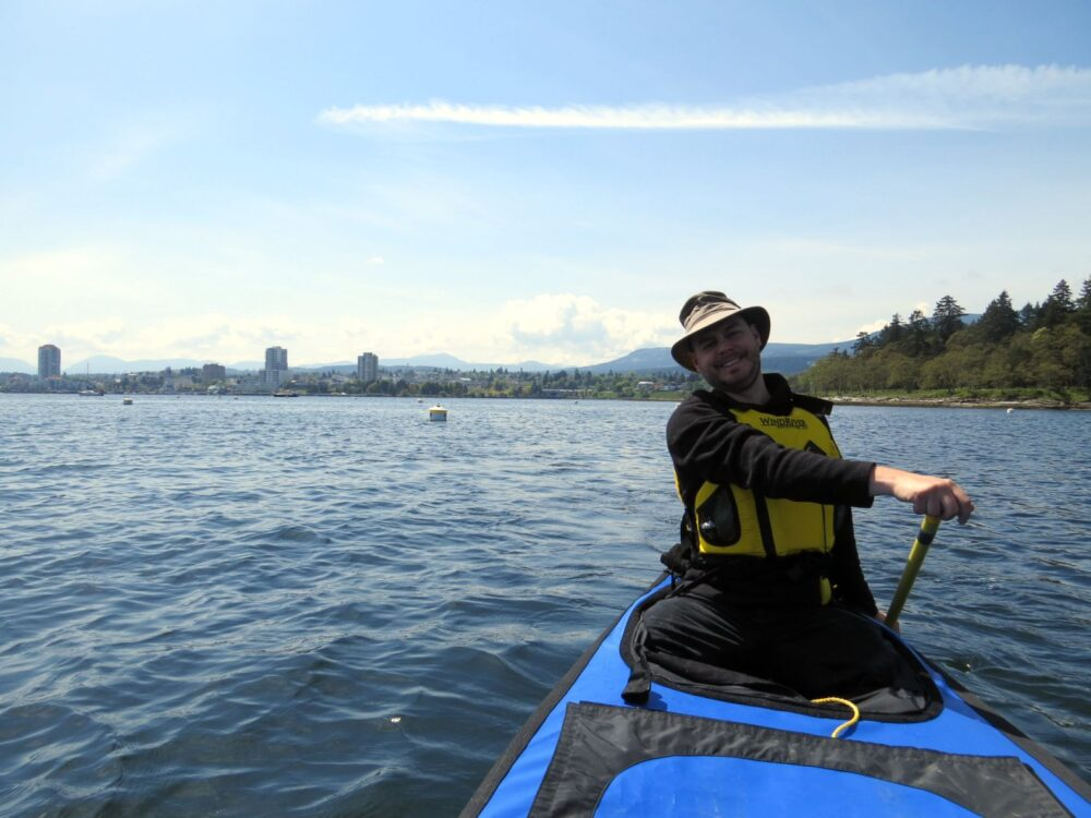 JR at the back of the canoe, paddling to Newcastle Island with Nanaimo skyline in background