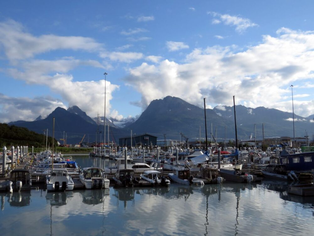 Harbour full of boats with mountain peaks behind