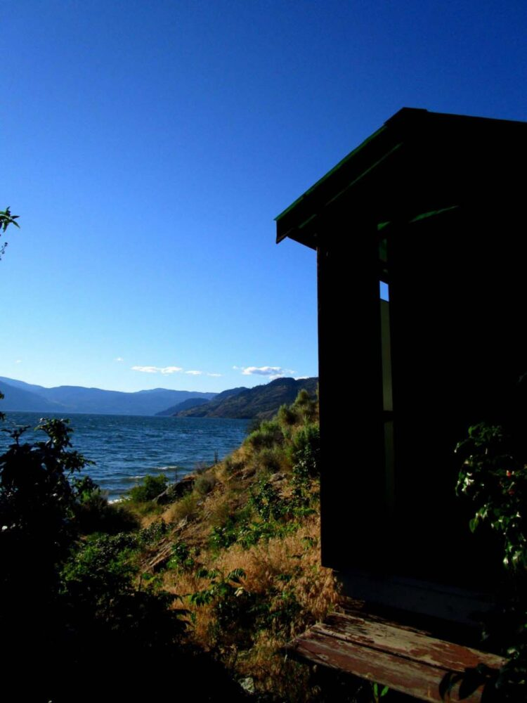 Dark outhouse building with Okanagan lake in background