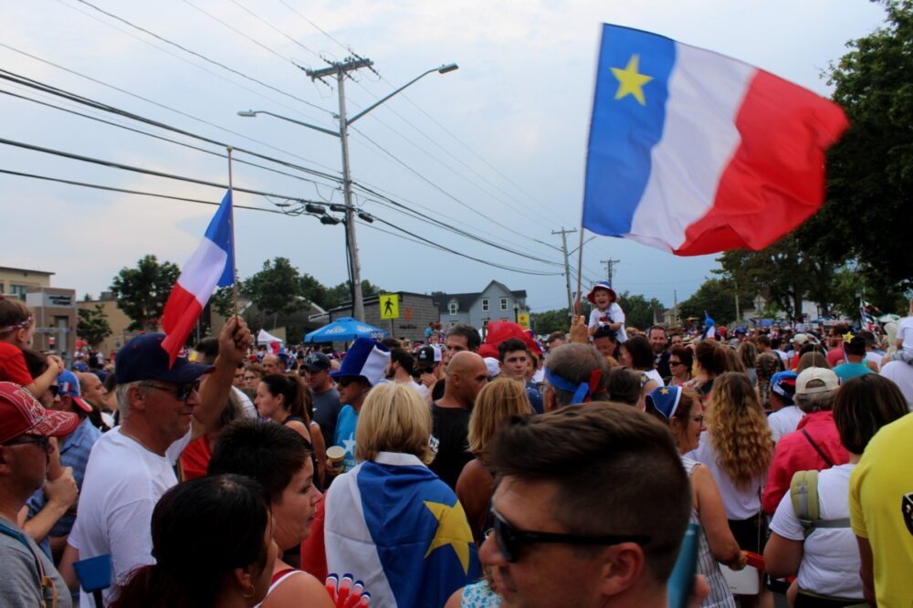 Crowd with Acadian flags and instruments at the Tintamarre