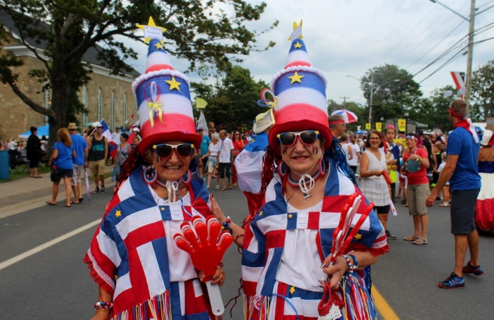 Two older ladies dressed head to toe in Acadian merchandise