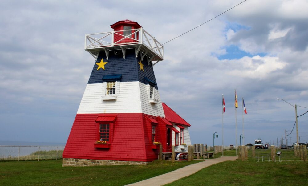 The lighthouse at Grande Anse is painted the Acadian flag colours