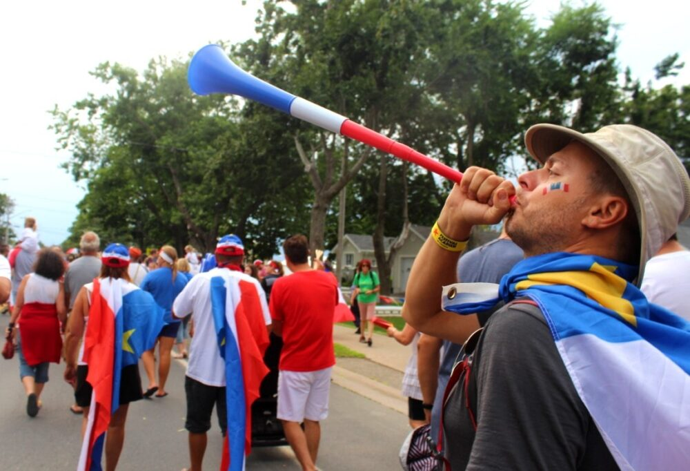 JR blowing a horn at the Tintamarre on Acadian Day in Caraquet, New Brunswick
