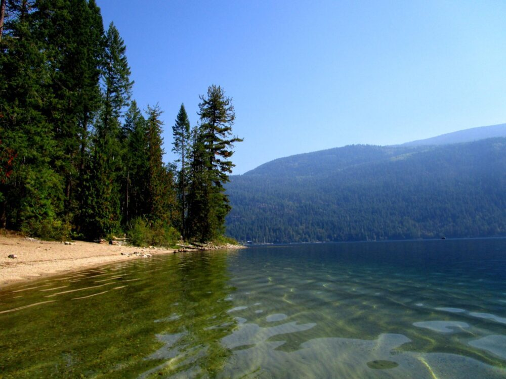 Canoe view of sandy beach on Christina Lake, with clear lake water, backdropped by forested hills