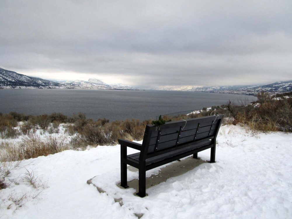 Bench surrounded by snow, with Okanagan Lake views