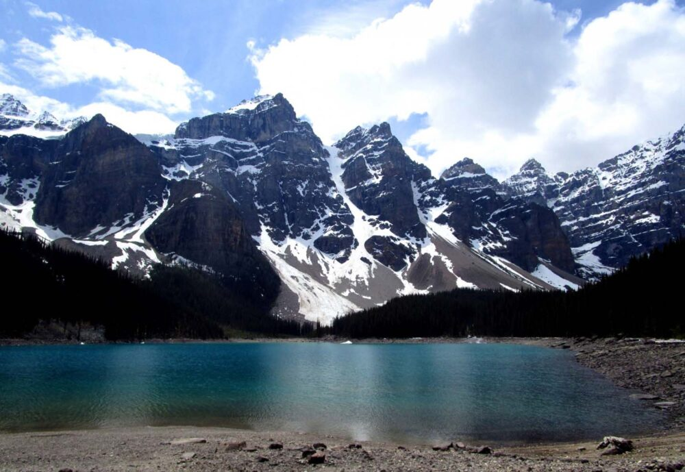 Snow covered peaks surrounding a glacial lake in Banff National Park, one of the most popular stops on any Vancouver to Calgary road trip