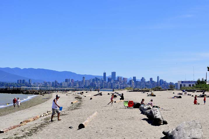 A sandy beach with high rise buildings and mountains behind
