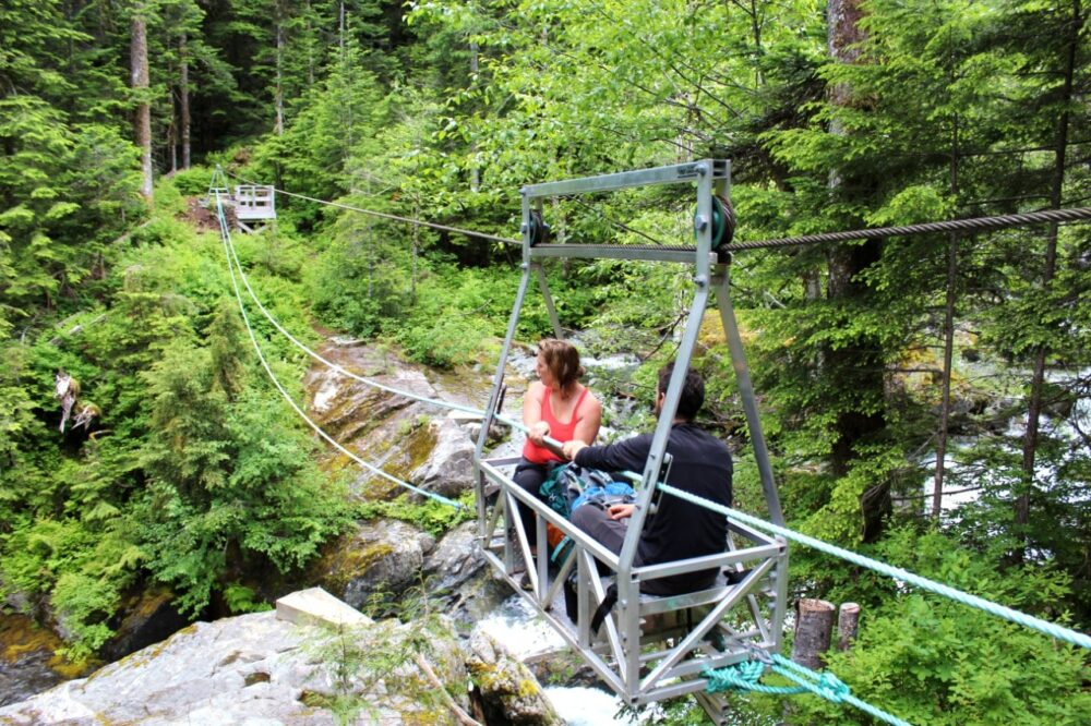 Two hikers pull themselves across a canyon in a metal cable car