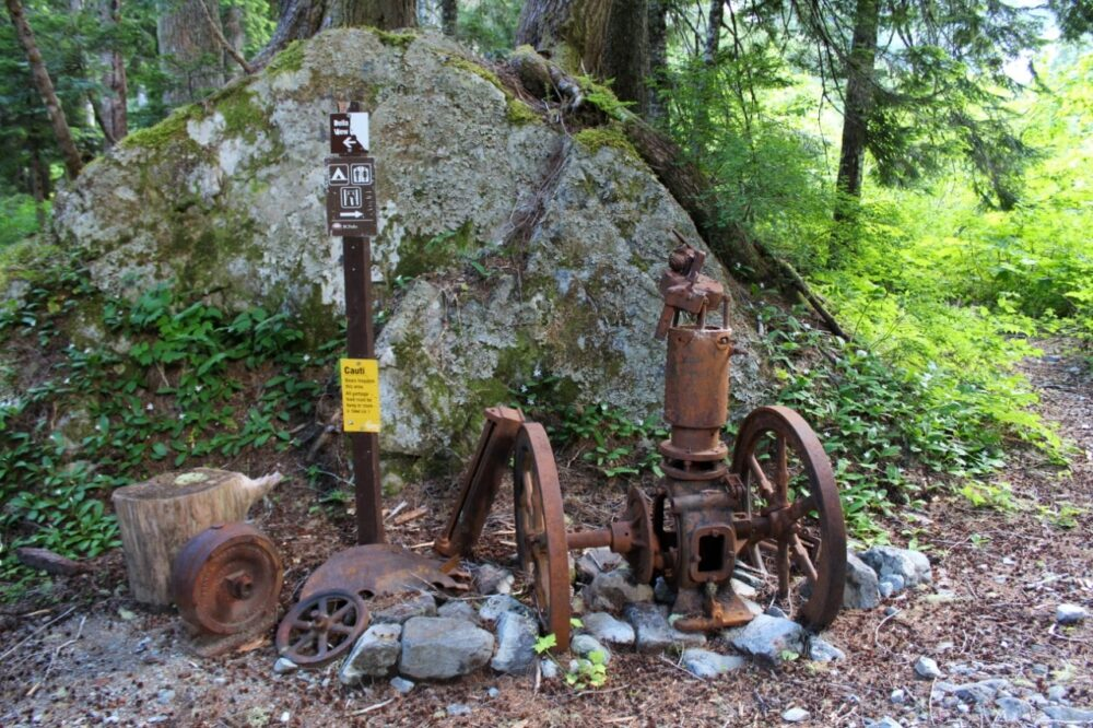 Rusted wheels and logging equipment next to the trail with campground signs